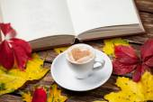 Autumn leafs, book and coffee cup on wooden table. — Stock Photo