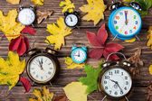 Autumn leafs and alarm clock on wooden table. — Stock Photo