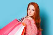 Redhead girl with shopping bags on blue background. — Stock Photo