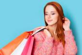 在蓝色背景上的购物袋的红发女孩. — 图库照片