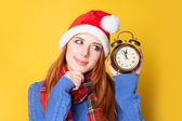 Redhead girl with alarm clock on yellow background. — Stock Photo