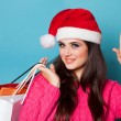 Brunette girl in christmas hat with shopping bags on blue backgr — Stock Photo #55948297