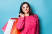 Brunette girl with shopping bags on blue background. — Stockfoto