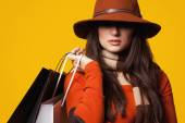 Style brunette girl with bags on yellow background. — Stockfoto
