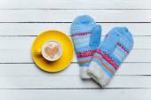 Coffee with heart shape symbol and mittens on wooden table. — Stock Photo