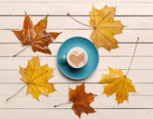 Cup of coffee and maple leafs on wooden table. — Stock Photo