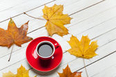 Cup of coffee and leafs on wooden table. — Stock Photo