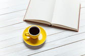 Book and cup of coffee on wooden table. — Stock fotografie