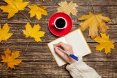 Female hand writing something in notebook near cup of coffee. — Stock Photo