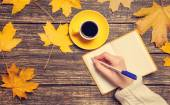 Female hand writing something in notebook near cup of coffee. — Stockfoto