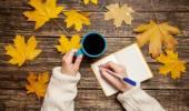 Female hand writing something in notebook near cup of coffee. — Zdjęcie stockowe