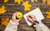 Female hand writing something in to notebook and holding apple — Stock Photo