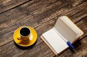 Coffee cup and notebook on a table. — Stock fotografie