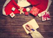 Female writing wish list in to notebook near christmas gifts — Stock Photo
