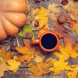 Pumpkin, leafs, chestnuts with cone and cup of coffee on a woode — Stock Photo #57176671
