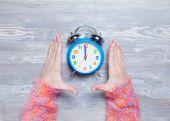 Female hands holding clock on a table. — ストック写真