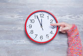 Female hands holding clock on a table. — Stock fotografie