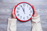 Female hands holding clock on a table. — Stock Photo