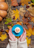 Female holding cup of coffee on autumn background. — Stock Photo