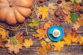 Pumpkin, leafs, chestnuts with cone and cup of coffee on a woode — Stock Photo