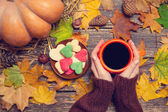 Female holding cup of coffee near cookies on autumn background. — Stock Photo