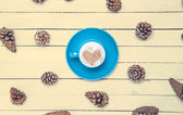 Cup of coffee and pine cone on a white table. — Stock Photo