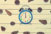 Relógio despertador e pinho abeto cone sobre uma mesa de madeira. — Fotografia Stock