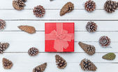 Gift box and and pine cone on a wooden table. — Stock Photo