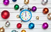 Alarm clock and christmas balls on white table. — Stock Photo