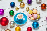 Cup of coffee and macaron with christmas toys on whte background — Stock Photo