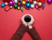 Girl holding cup of coffee near christmas toys. — Stock Photo