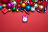 Alarm clock and christmas toys on red table. — Stock Photo