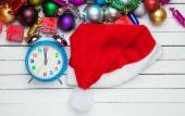 Alarm clock and santa's hat with christmas gifts. — Stock Photo