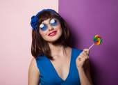 Fanny girl with lolipop on pink and violet background. — Stock Photo