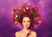 Beautiful redhead girl with christmas toys and canes in hair on — Stock Photo