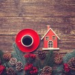 Coffee cup and toy house on a wooden table. — Stock Photo #57597613