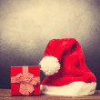 Red Santas hat and gift box on a wooden table. — Stock Photo #57597937
