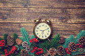 Alarm clock near Pine branches on wooden table. — Stock Photo