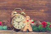 Alarm clock near Pine branches and gingerbread on wooden table. — Stock Photo