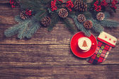 Hot cappuccino with christmas tree shape on a wooden table near  — Stock Photo