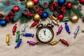 Alarm clock near Pine branches on a table. — Stock Photo
