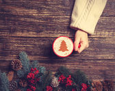 Female holding cup of coffee with cream christmas tree on a tabl — Stock Photo