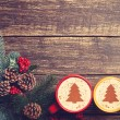 Two cups with christmas tree shape near branch on a wooden table — Stock Photo #58971947