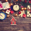 Toy house and christmas gifts, gingerbread, alarm clocks — Stock Photo #58972125