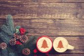 Two cups with christmas tree shape near branch on a wooden table — Stock Photo