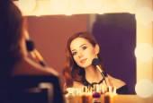 Beautiful redhead women appling makeup near mirror — Stock Photo