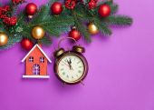 Alarm clock and toy house with pine branch — Stock Photo