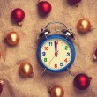 Retro alarm clock with gold and red balls on jute background. — Stock Photo #59050149