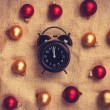 Retro alarm clock with gold and red balls on jute background. — Stock Photo #59050177