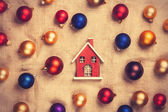 Toy house with red and gold balls on jute background. — Stock Photo